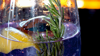 A mixed drink with a lemon wedge and sprig of rosemary served at the cocktail bar 16 - A Handmade Experience at The M Resort Spa Casino in Las Vegas, Nevada.