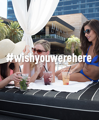 "ladies enjoying drinks by the pool with text ""#WishYouWereHere"""