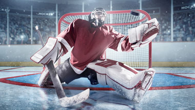 hockey goalie in front of net stopping the puck
