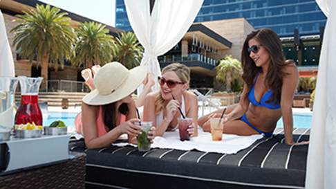 Three women lounge in a cabana, sipping drinks, at M Resort