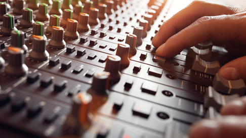 An operator makes adjustments to a soundboard. The M Resort offers full audio and visual services for meetings and events.