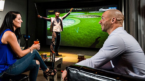 A couple shares a drink inside Top Golf Swingsuite
