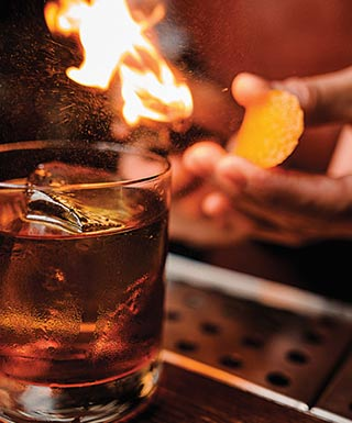 A glass of liquor sits on a bar as a bartender lights a flame.