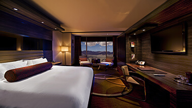 The king-size bed, executive desk with leather chair and conversation area in front of the window showing a view of the mountains of Las Vegas in the Executive Resort Room at The M Resort Spa Casino Hotel.
