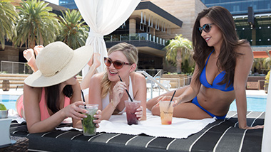 3 girls poolside, in a cabana with drinks