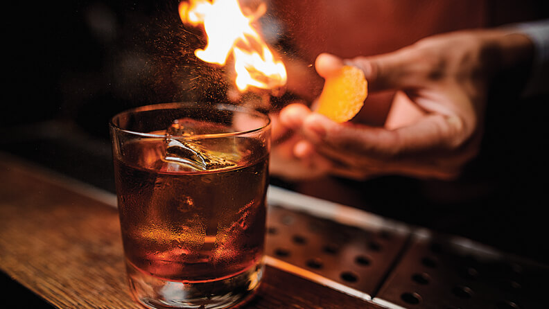 A glass of liquor on a bar with a bartender lighting a flame behind it.